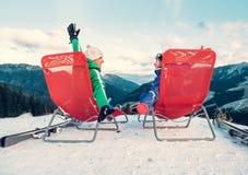 Deux skieurs détendent dans les chiars sur le dessus de montagne Image stock
