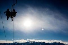 Deux skieurs dans un télésiège éclairé à contre-jour par le soleil. photos libres de droits