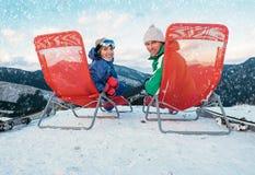 Deux skieurs de sourire s'asseyent dans la chaise longue sur le dessus de montagne Photos stock