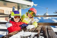 Deux skieurs s'asseyant à la table du café de montagne Photographie stock