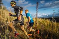 Deux skyrunners de coureurs d'hommes courant la traînée ascendante dans l'herbe sur le fond de ciel bleu Photographie stock