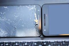 Deux smartphones sur le clavier d'ordinateur portable Photos libres de droits