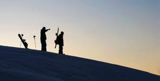 Deux snowboarders dans le coucher du soleil Photographie stock