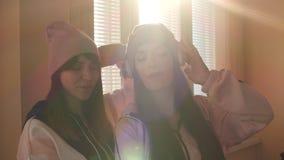 Deux soeurs actives dans la musique de écoute de chapeaux et d'écouteurs banque de vidéos