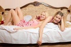 Deux soeurs adultes dans des pyjamas se trouvant sur le lit blanc Photographie stock