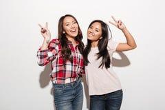 Deux soeurs assez gaies de dames d'Asiatique montrant la paix font des gestes photographie stock