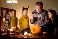 Deux soeurs assez jeunes dans des costumes de Halloween et leur grand-papa découpant un potiron ensemble Images libres de droits