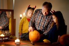 Deux soeurs assez jeunes dans des costumes de Halloween et leur grand-papa découpant un potiron ensemble Photo libre de droits