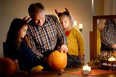 Deux soeurs assez jeunes dans des costumes de Halloween et leur grand-papa découpant un potiron ensemble Photos libres de droits