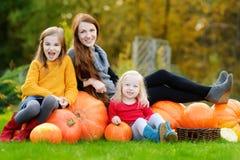 Deux soeurs assez petites et leur mère ayant l'amusement ensemble sur une correction de potiron Photographie stock