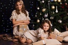 Deux soeurs avec des cadeaux de nouvelle année s'approchent de Noël Images stock
