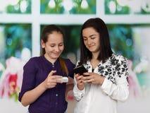 Deux soeurs avec des téléphones portables Images stock