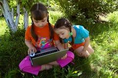 Deux soeurs avec l'ordinateur portatif Photographie stock libre de droits