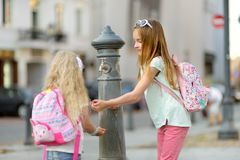 Deux soeurs ayant l'amusement avec la fontaine d'eau potable le jour chaud et ensoleillé d'été Photographie stock libre de droits