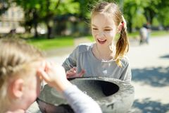 Deux soeurs ayant l'amusement avec la fontaine d'eau potable le jour chaud et ensoleillé d'été image stock