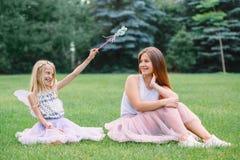 Deux soeurs caucasiennes drôles de sourire de filles utilisant les jupes roses de Tulle de tutu dans le pré de forêt de parc au c Image stock