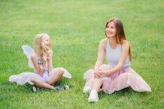 Deux soeurs caucasiennes drôles de sourire de filles utilisant les jupes roses de Tulle de tutu dans le pré de forêt de parc au c Photographie stock