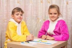Deux soeurs cinq et sept ans ont ensemble moulé des métiers d'argile Image libre de droits