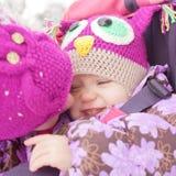 Deux soeurs dans des chapeaux tricotés aiment des hiboux Photographie stock libre de droits