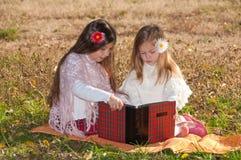 Deux soeurs de filles ont affiché le livre sur l'herbe Photo libre de droits
