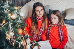 Deux soeurs de filles ont pour détendre et amusement dans une chambre décorée pendant Noël et la nouvelle année Photos stock