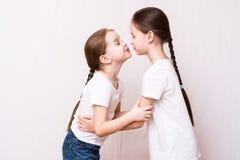 Deux soeurs de filles s'embrassent en se réunissant photos stock