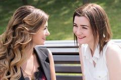 Deux soeurs de jeune femme s'asseyant sur un banc en parc Image stock