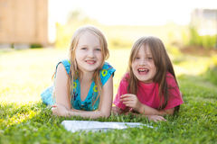 Deux soeurs de shooler lisant dehors, ayant l'amusement Photo libre de droits