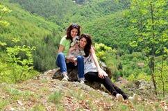 Deux soeurs de sourire dans la montagne avec leur chien Images stock