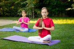 Deux soeurs de sourire pratiquant le yoga sur l'herbe au parc Photos libres de droits