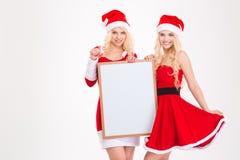 Deux soeurs en père noël costume la pose avec le conseil vide Images stock