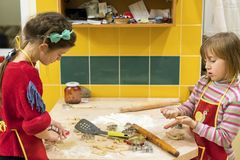 Deux soeurs 5 et 7 ans dans la cuisine font des biscuits de pâtisserie Assistant du ` s de deux mamans images stock