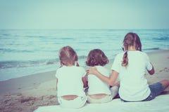 Deux soeurs et frère s'asseyant sur la plage Image libre de droits