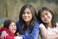 Deux soeurs et leur petit frère handicapé Photos stock