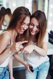 Deux soeurs examinant le produit de base écrèment enregistrer un nouveau guide d'application de maquillage pour leur vlog de beau images libres de droits