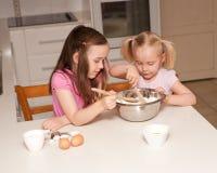 Deux soeurs font des pains cuire au four Photo stock