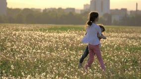 Deux soeurs heureuses ont étreint entourer sur la clairière des pissenlits dans la perspective des bâtiments de ville dehors Enfa clips vidéos