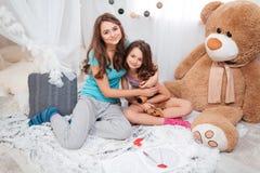 Deux soeurs heureuses s'asseyant et étreignant chez la pièce des enfants Image stock