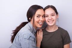 Deux soeurs heureuses sur le fond gris Image libre de droits