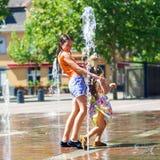 Deux soeurs jouant avec l'éclaboussure de fontaine Photo stock