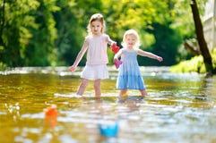 Deux soeurs jouant avec les bateaux de papier par une rivière Photographie stock