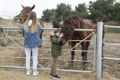 Deux soeurs jouant des chevaux dans un abri de Rojales image libre de droits