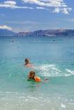 Deux soeurs jouant des jeux et nageant en mer Photo stock