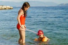 Deux soeurs jouant des jeux et nageant en mer Images stock
