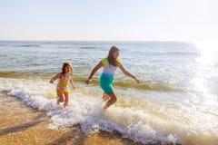 Deux soeurs jouant sur la plage au coucher du soleil Photographie stock