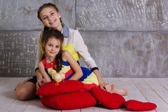 Deux soeurs jouent avec le poussin Photographie stock