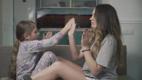 Deux soeurs jouent le jeu de Pat-un-gâteau se reposant sur le divan dans le salon ensemble Relations de soeurs banque de vidéos