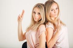 Deux soeurs jumelles et leur ami montrent le geste d'arme à feu Image libre de droits
