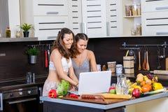 Deux soeurs jumelles recherchant la recette de salade sur l'Internet Images stock