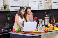 Deux soeurs jumelles recherchant la recette de salade sur l'Internet Image stock